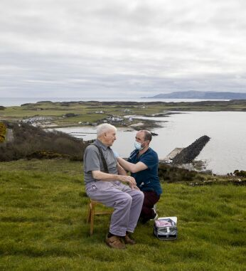 Mr McBurney's picture of Dr r Gavin Chestnutt vaccinating a 92-year-old man in his front garden on Rathlin Island, Northern Ireland for Sky News