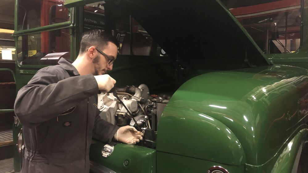 Alex, checking the oil levels of a vintage green bus