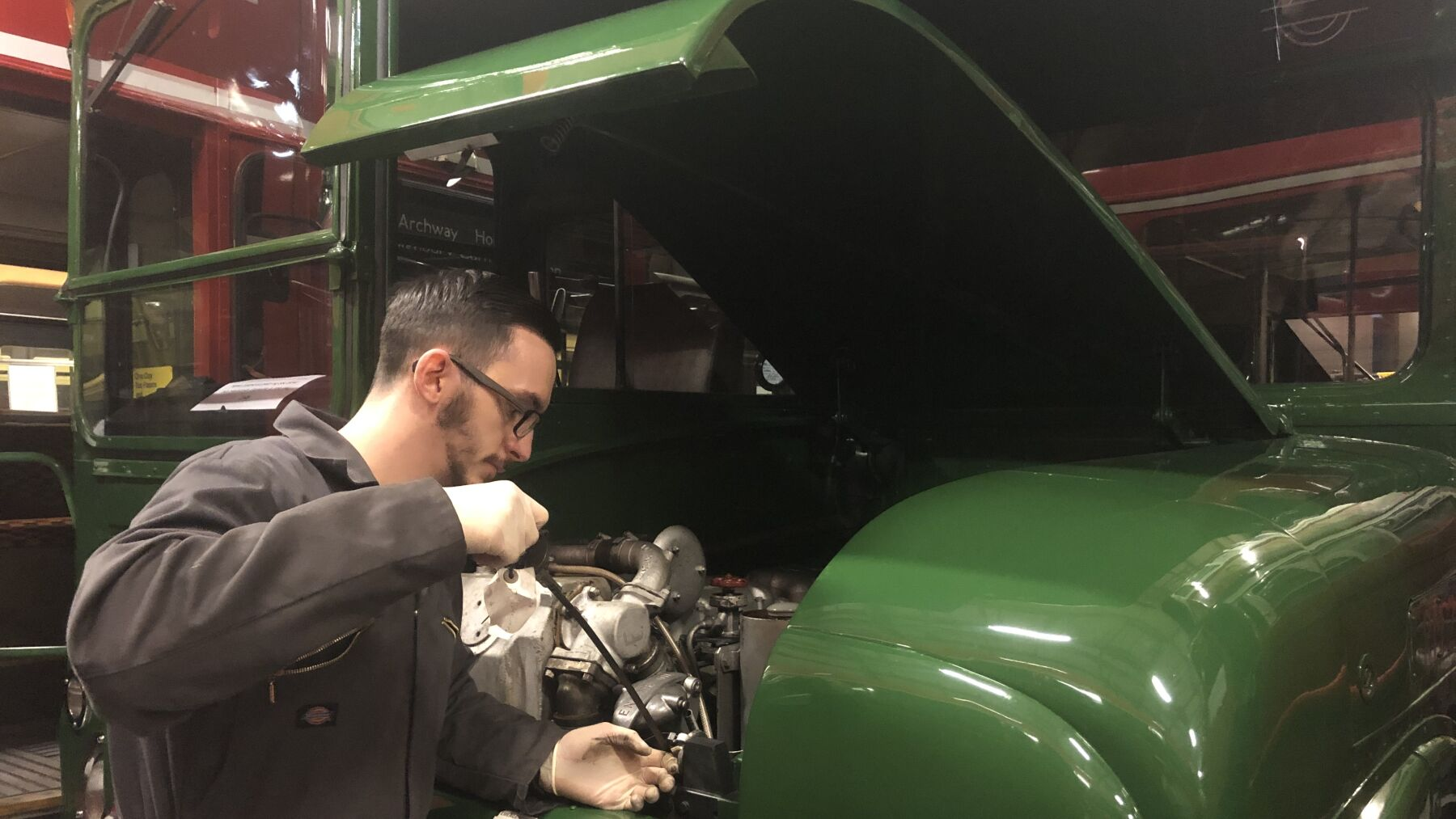 Alex checking the oil levels on a vintage London bus