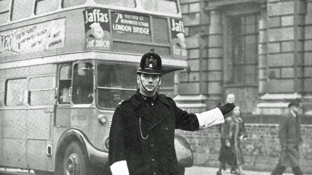Picture of a police officer in the 1940s directing traffic in London with a bus in the background; credit Leonard Bentley, Flickr