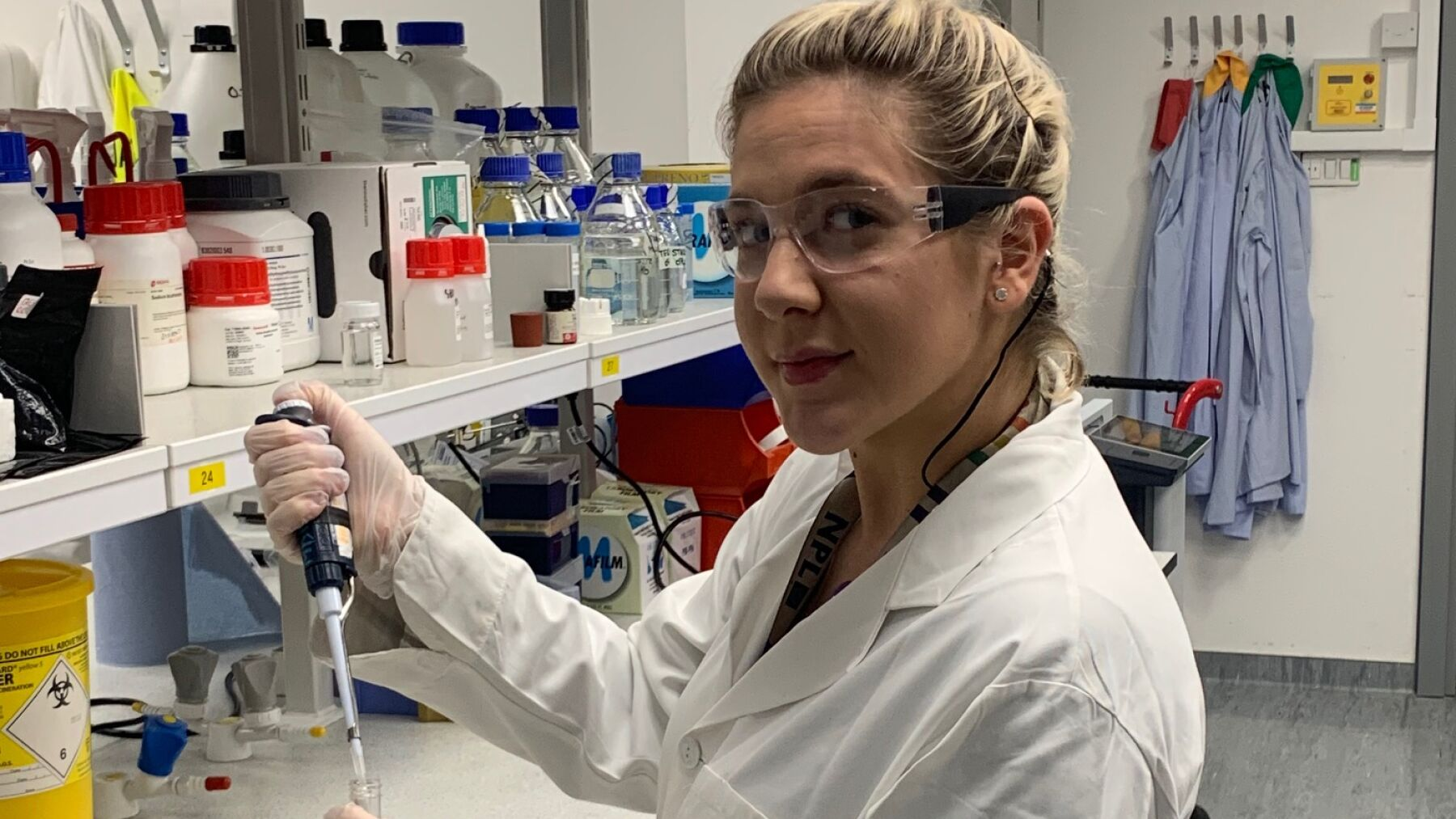 Jessica a lab apprentice  at King's College London University holding a pipet towards a flask and looking towards the camera