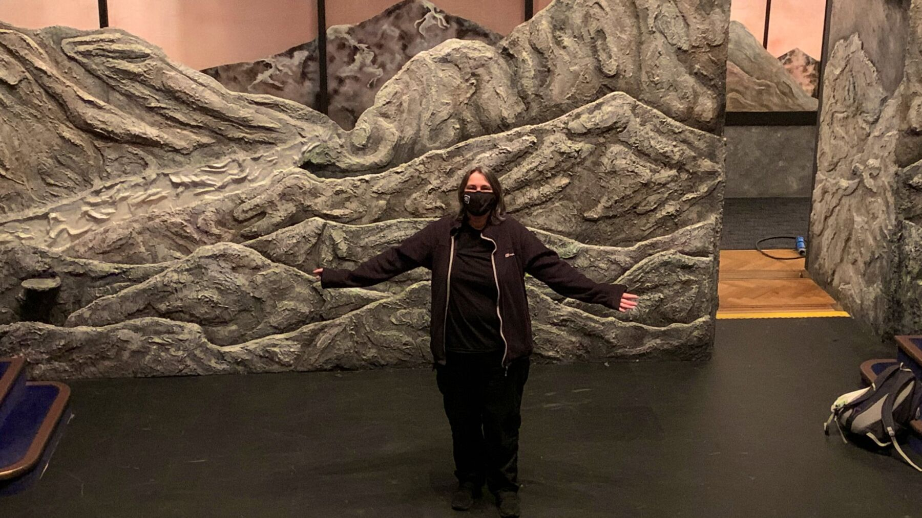 Lin stood with her arms outstretched on a set of caves and rocks