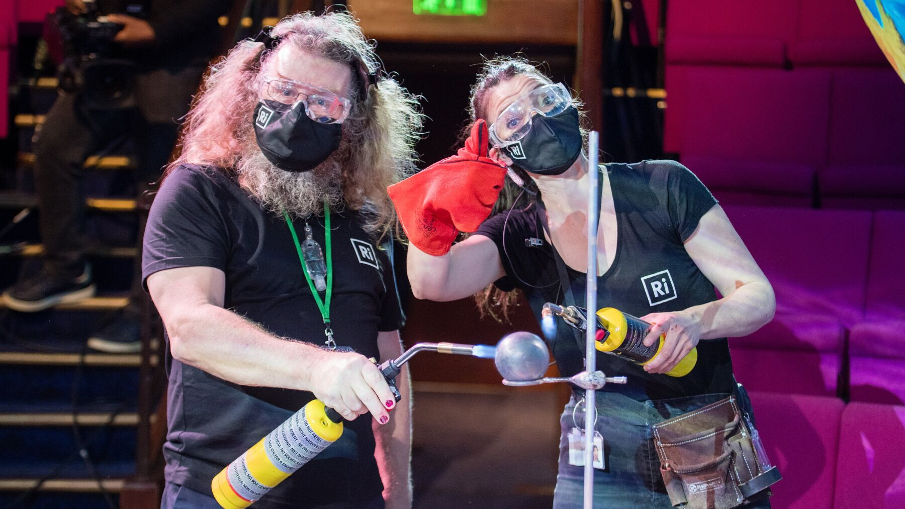 Malcolm with fellow RI participant Fran Scott. Both are holding blow torches towards a cannon ball, and wearing face masks.