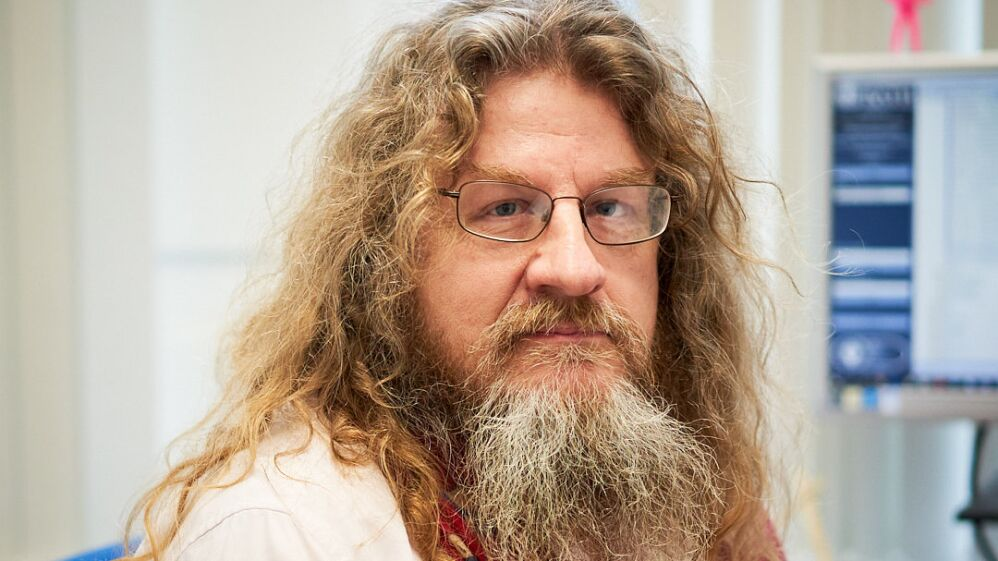 Malcolm Holley looking into the camera. He's 58 with long hair, a beard and glasses. He's wearing a white lab coat.